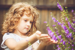 Curly baby with flowers in her hand. Toning photo. Instagram fil Stock Photos