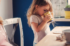 Cute baby girl drinking tea for breakfast in sunny kitchen Stock Photography