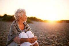 Dame âgée s'asseyant sur la plage regardant loin le copyspace Images libres de droits