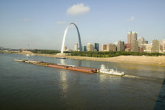 Daytime view of tug boat pushing barge down Mississippi  River in front of Gateway Arch and skyline of St. Louis, Missouri as seen Royalty Free Stock Images