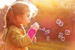 De blazende zeepbels van het kindmeisje openlucht Stock Foto