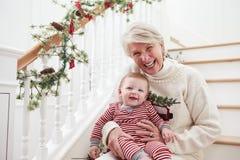 De grootmoeder met Kleindochter zit op Treden bij Kerstmis Royalty-vrije Stock Foto