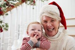 De grootmoeder met Kleindochter zit op Treden bij Kerstmis Stock Fotografie