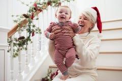 De grootmoeder met Kleindochter zit op Treden bij Kerstmis Royalty-vrije Stock Afbeeldingen