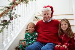 De grootvader met Kleinkinderen zit op Treden bij Kerstmis Royalty-vrije Stock Foto's
