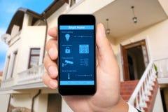 De mannelijke hand houdt een telefoon met systeem slim huis op de achtergrond Royalty-vrije Stock Afbeelding