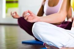 De vrouwen in de gymnastiek die yoga doen oefenen voor geschiktheid uit Royalty-vrije Stock Foto's