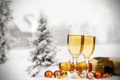 Decorazioni e champagne di Natale contro il fondo di inverno Immagini Stock