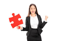 Delighted businesswoman holding a piece of puzzle Stock Images