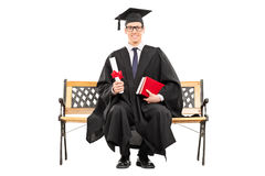 Delighted college graduate sitting on a bench Stock Image