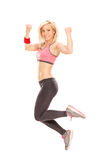 Delighted female athlete jumping out of joy Stock Photography