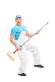 Delighted house painter playing guitar on a paint roller Stock Images