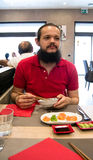 Delighted man / customer in red shirt eating Chinese / Japanese food in a restaurant Stock Photos
