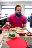 Delighted man / customer in red shirt eating Chinese / Japanese food in a restaurant Stock Image