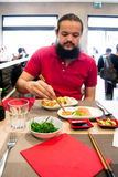 Delighted man / customer in red shirt eating Chinese / Japanese food in a restaurant Royalty Free Stock Images