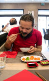 Delighted man / customer in red shirt eating Chinese / Japanese food in a restaurant Royalty Free Stock Photo