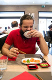 Delighted man / customer in red shirt eating Chinese / Japanese food in a restaurant Stock Photo