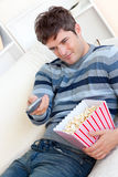 Delighted man eating popcorn and holding a remote Royalty Free Stock Photography