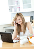Delighted woman using a laptop in the kitchen Stock Images