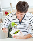 Delighted young man eating a healthy salad Stock Photo