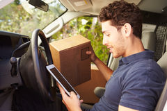 Delivery Driver Sitting In Van Using Digital Tablet Royalty Free Stock Photos