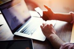 Den bakre sikten av affärsmannen räcker den upptagna användande mobiltelefonen på kontorsskrivbordet Arkivfoto