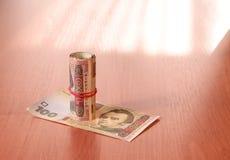 Deposite o rolo do hryvnia ucraniano na tabela Foto de Stock Royalty Free