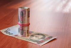 Deposite o rolo do hryvnia ucraniano na tabela Fotografia de Stock