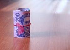 Deposite o rolo do hryvnia ucraniano na tabela Foto de Stock