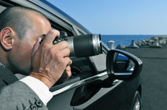 Detective or paparazzi taking photos from inside a car Royalty Free Stock Photo
