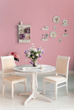 Dining room interior with flowers decorative plates pink wall an Stock Photo