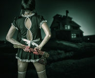 Dirty woman stands back holding a bloody ax Royalty Free Stock Images