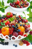 Dish with fresh seasonal fruit and berries on table, vertical Royalty Free Stock Photos