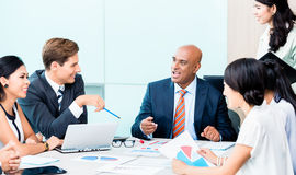 Diversity team in business development meeting with charts Royalty Free Stock Photo
