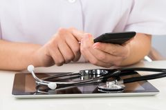Doctor with mobile phone and digital tablet Royalty Free Stock Photos