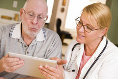 Doctor or Nurse Talking to Senior Man with Touch Pad Royalty Free Stock Images
