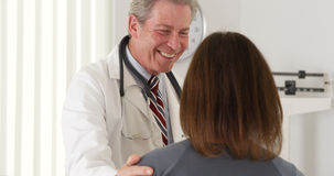 Doctor reassuring elderly patient of quick recovery Stock Photos