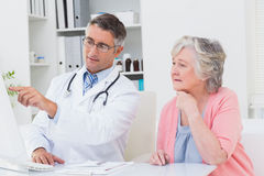 Doctor showing reports to senior patient on computer Stock Photo
