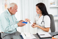 Doctor shows the patient how to use daily dose pills Stock Photo