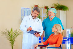 Doctor and surgeon consulting patient about medication Stock Photo