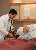 Doctor taking senior blood pressure Royalty Free Stock Images