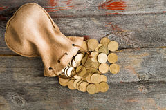 Dollar coins spilling out of a drawstring pouch Royalty Free Stock Image