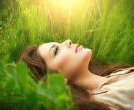 Donna di bellezza che si trova sul campo e sul sogno Fotografia Stock
