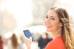 Donna felice che cammina nella via facendo uso di uno smartphone Fotografia Stock Libera da Diritti