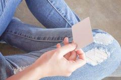 Donna in jeans lacerati che si siedono sulla terra Immagine Stock