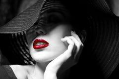 Donna misteriosa in black hat. Labbra rosse Immagini Stock