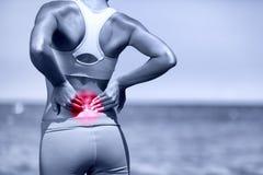 Douleur dorsale Femme courante sportive avec la lésion dorsale Image stock