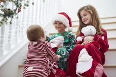 Drie Kinderen die op Treden met Kerstmiskousen zitten Stock Foto