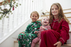 Drie Kinderen die in Pyjama's op Treden bij Kerstmis zitten Royalty-vrije Stock Foto