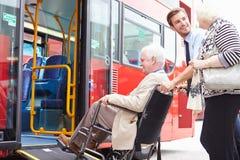 Driver Helping Senior Couple Board Bus Via Wheelchair Ramp Stock Image